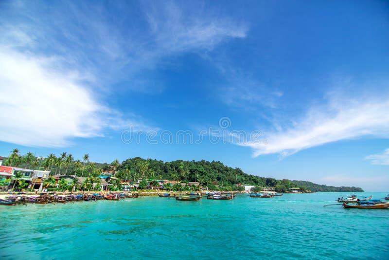 Barcos de pesca tailandeses tradicionais envolvidos com fitas coloridas Contra o contexto de uma ilha tropical fotos de stock royalty free