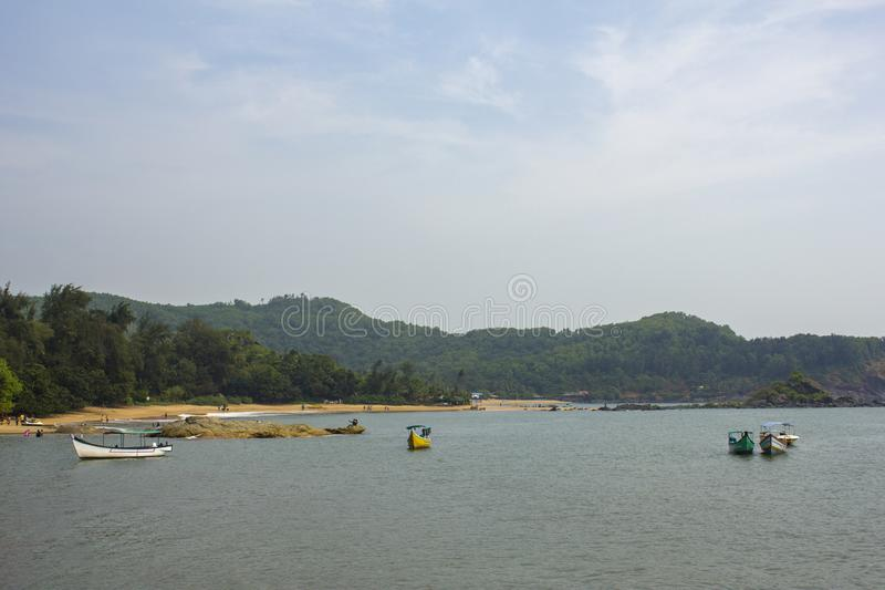 Barcos de prazer com as barracas no mar perto da costa na perspectiva de um Sandy Beach e dos montes com uma floresta verde, vist imagens de stock