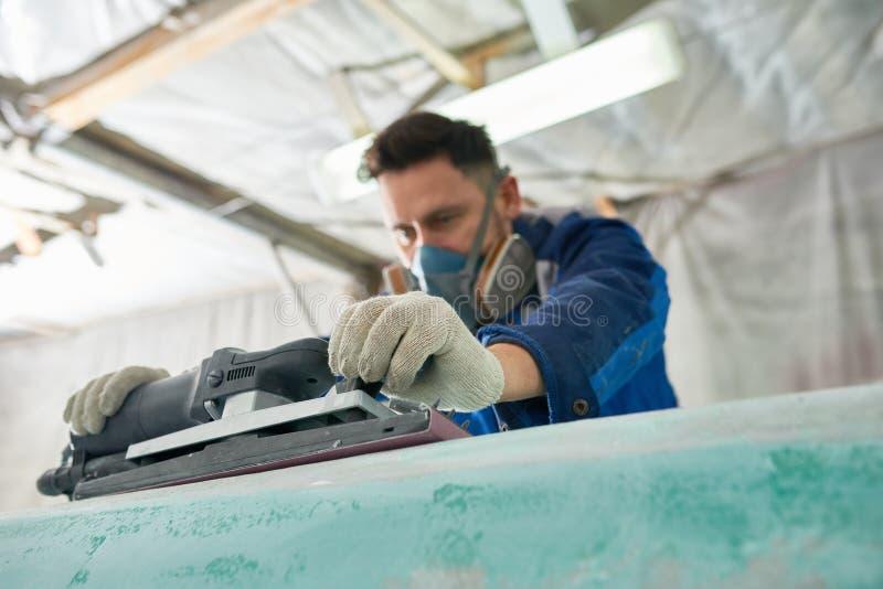 Barcos de pulido del hombre en taller imagen de archivo