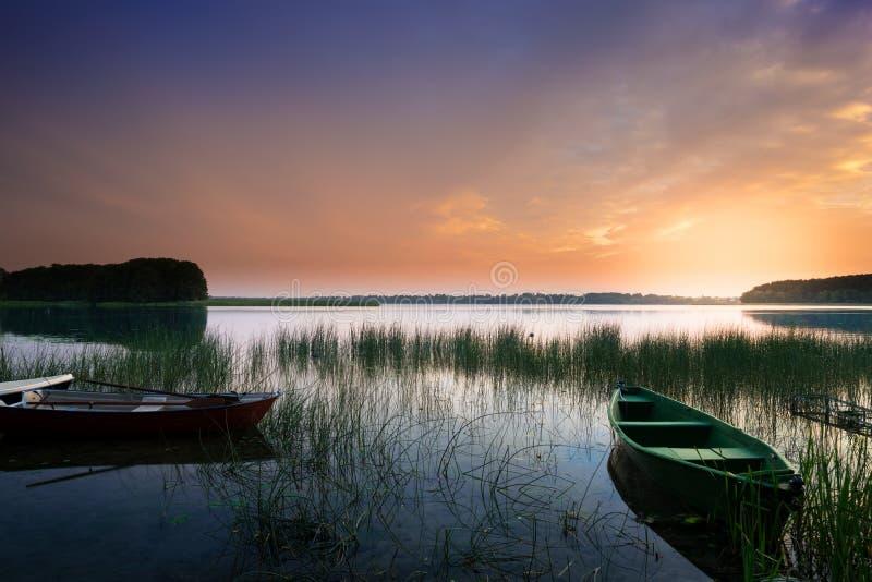 Barcos de rowing en puesta del sol imagenes de archivo