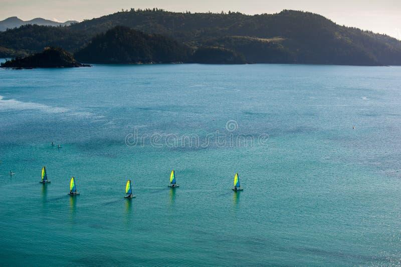 Barcos de vela/catamarãs com as velas coloridas na água na frente do resort da ilha foto de stock