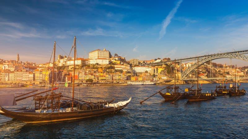 Barcos del vino de Oporto en la costa con el puente de Dom Luis y el o fotografía de archivo libre de regalías