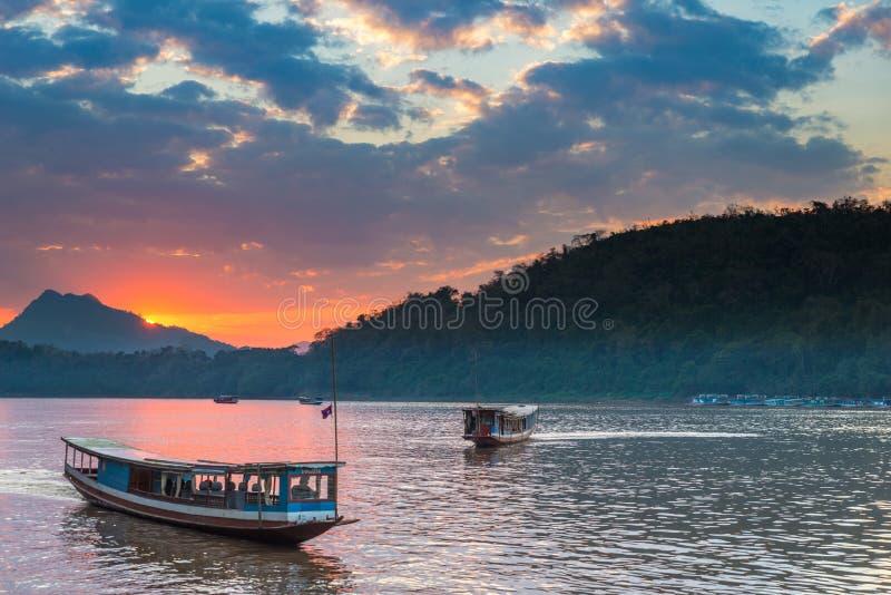 Barcos em Mekong River em Luang Prabang Laos, céu dramático do por do sol, mochileiro famoso do destino do curso em 3Sudeste Asiá imagens de stock