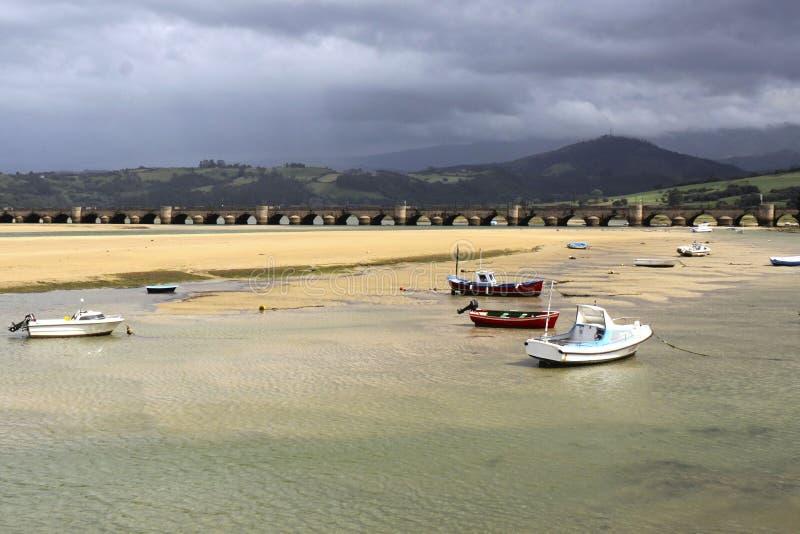 Barcos en la costa y un puente, en San Vicente de la Barquera imagenes de archivo