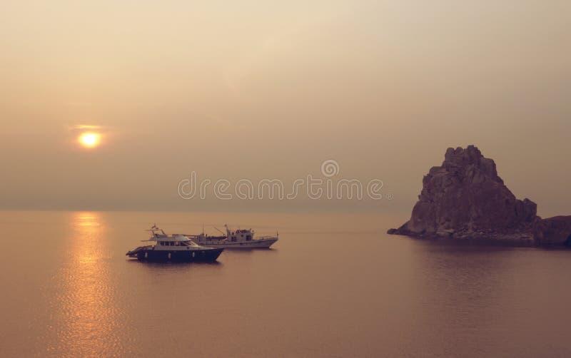 Barcos en la isla de Olkhon de la puesta del sol en el lago Baikal fotografía de archivo libre de regalías