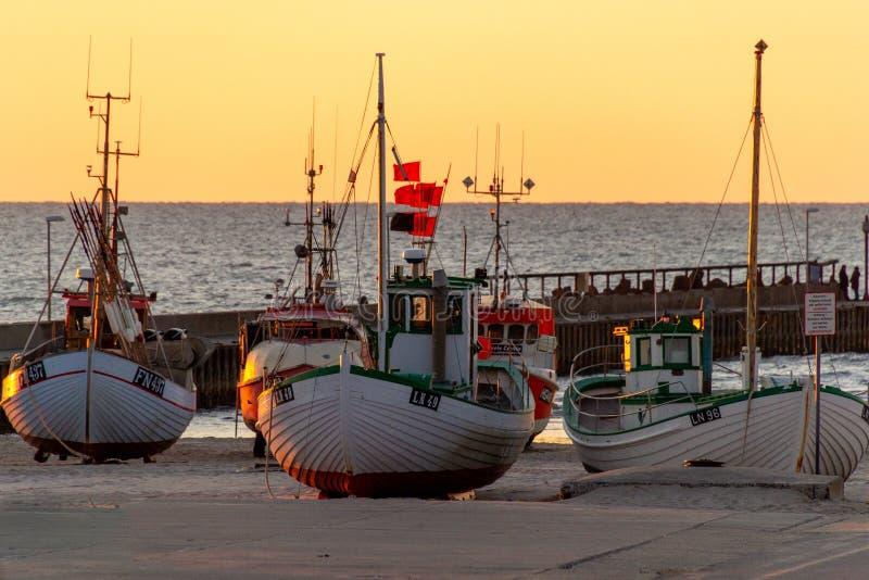 Barcos en la playa en Løkken en la puesta del sol foto de archivo