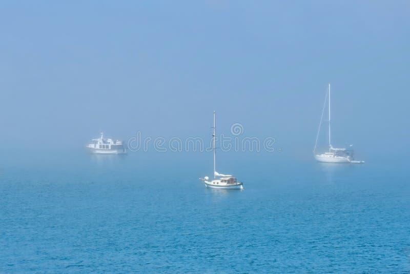 Barcos en niebla Barcos de navegación amarrados en un puerto brumoso imágenes de archivo libres de regalías