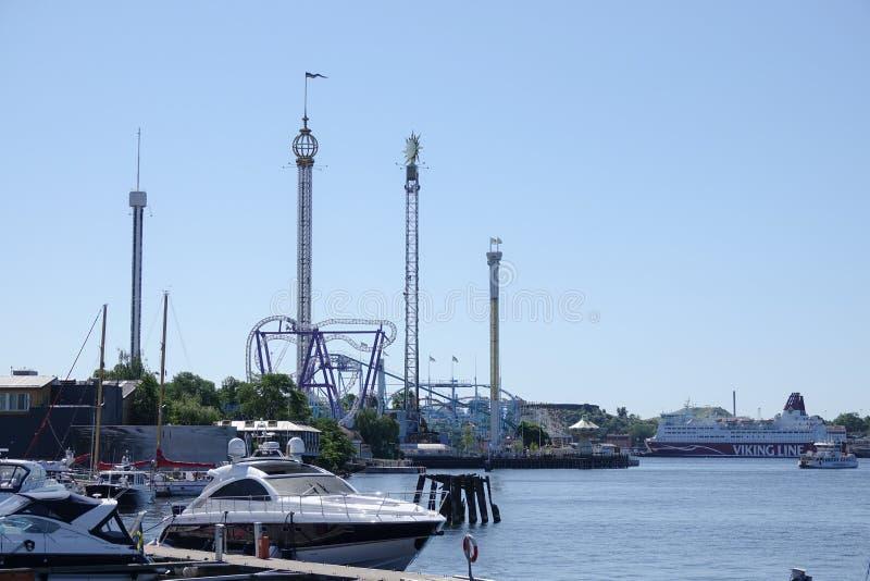 Barcos a motor e parque de diversões Gröna/Grona Lund no fundo imagens de stock