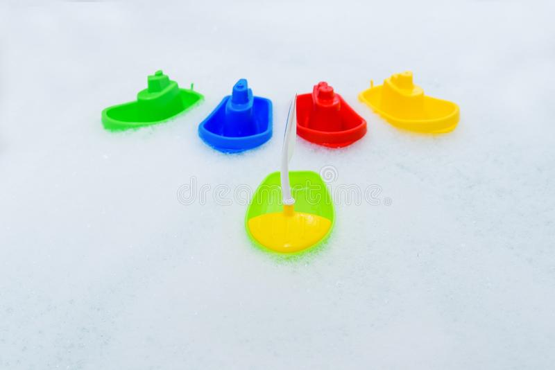 Barcos multicolores pl?sticos del juguete en ba?o de la espuma fotos de archivo