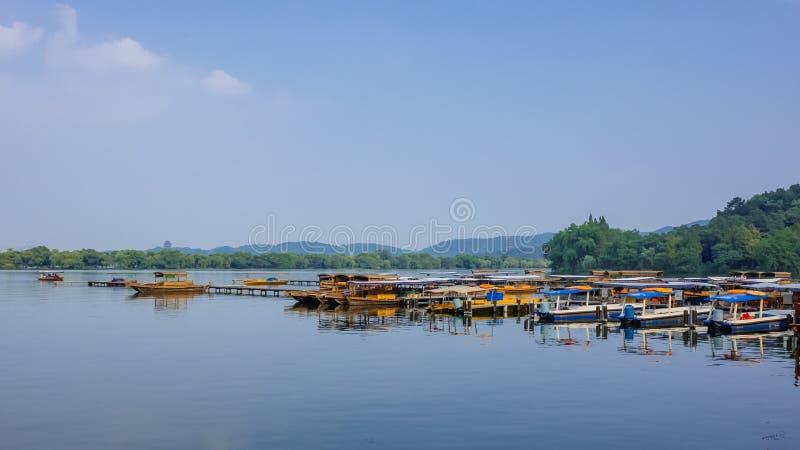 Barcos na doca sobre a água calma do lago ocidental, com os montes na distância, em Hangzhou, China fotos de stock royalty free