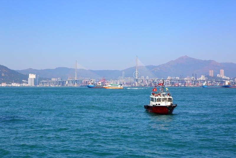 Barcos no porto de Hong Kong e na ponte dos Stonecutters fotografia de stock