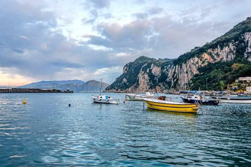 Barcos no porto principal da ilha de Capri sob céus nebulosos foto de stock