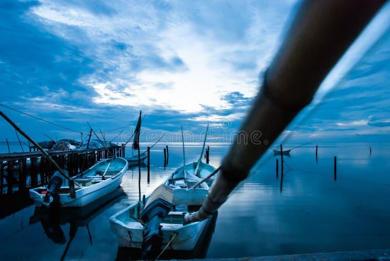 Barcos o canoas en el muelle y la puesta del sol azul en Campeche México fotografía de archivo