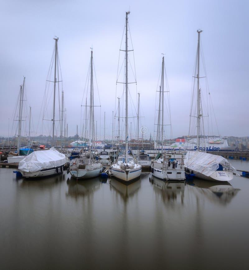 Barcos parqueados en aún agua durante una mañana de niebla imagen de archivo