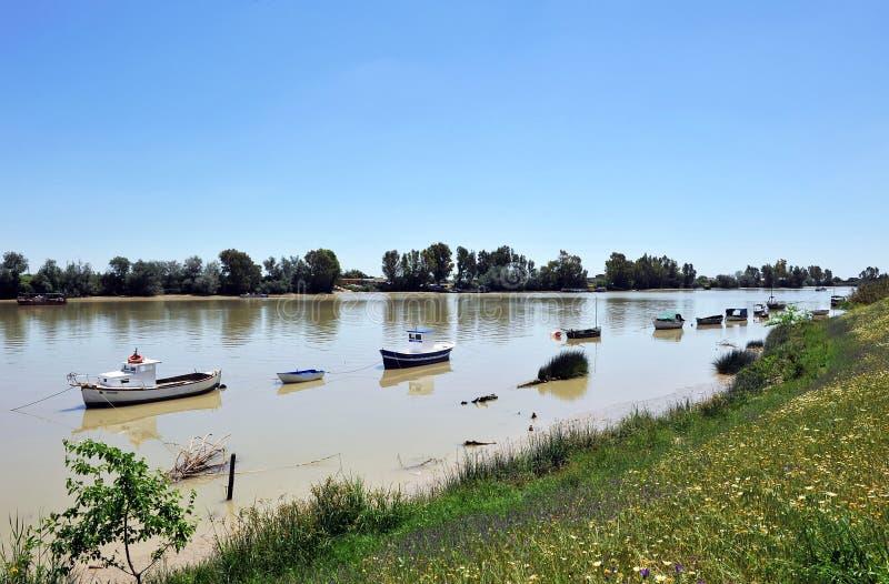 Barcos pequenos no rio como passa através de Coria del Rio, província de Sevilha, a Andaluzia de Guadalquivir, Espanha fotos de stock royalty free