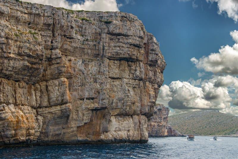 Barcos que pasan los acantilados enormes del parque nacional Croacia de Kornati imagenes de archivo