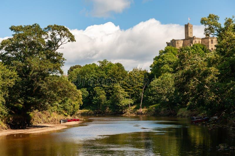 Barcos a remo amarrados na base do Castelo de Warkworth, Morpeth, Northumberland, Reino Unido, num dia ensolarado imagens de stock royalty free