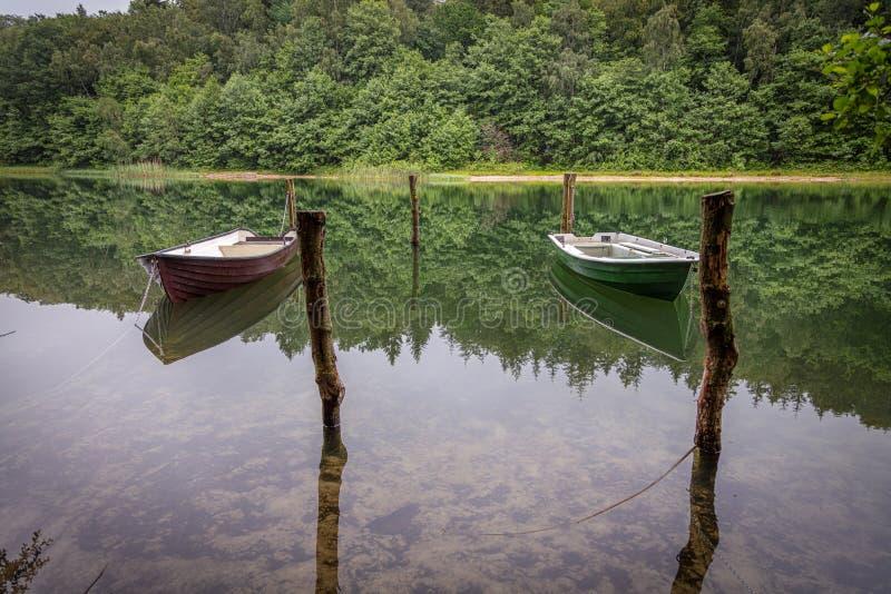barcos a remos acorrentados que nadam em um lago imagens de stock royalty free