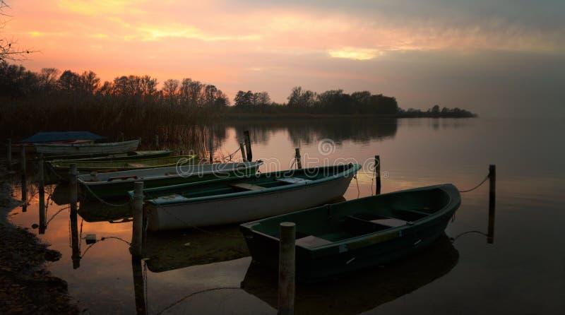Barcos a remos na costa do lago após o por do sol, paisagem cênico com espaço da cópia foto de stock