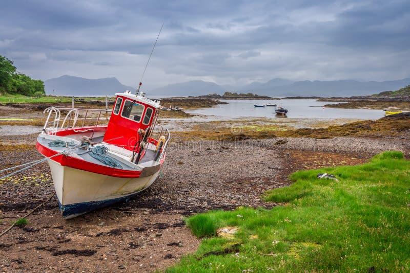 Barcos rojos en la costa durante la bajamar, Escocia imagenes de archivo