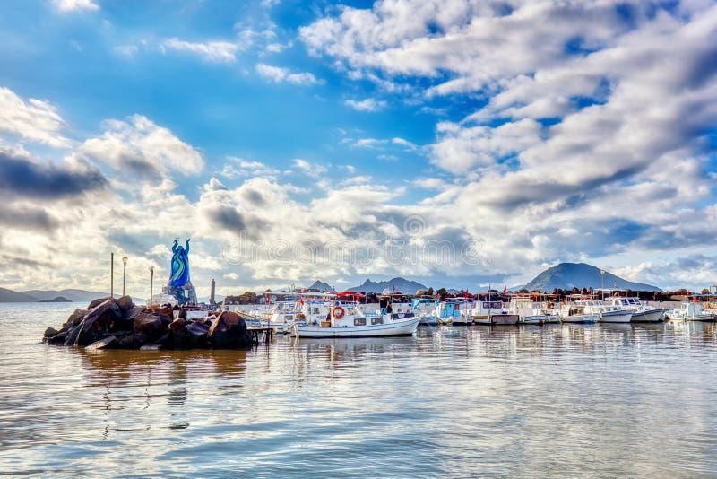 Barcos tradicionais de madeira atracados no porto e estátua turca de amizade grega Aegean em Turgutreis, Bodrum, Mugla, foto de stock