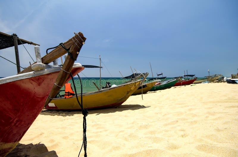 Barcos tradicionales del pescador en la playa arenosa fondo del día soleado brillante y del cielo azul foto de archivo