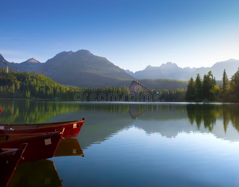 Barcos vermelhos no lago da montanha em Tatra alto. Strbske Pleso, Slovaki foto de stock
