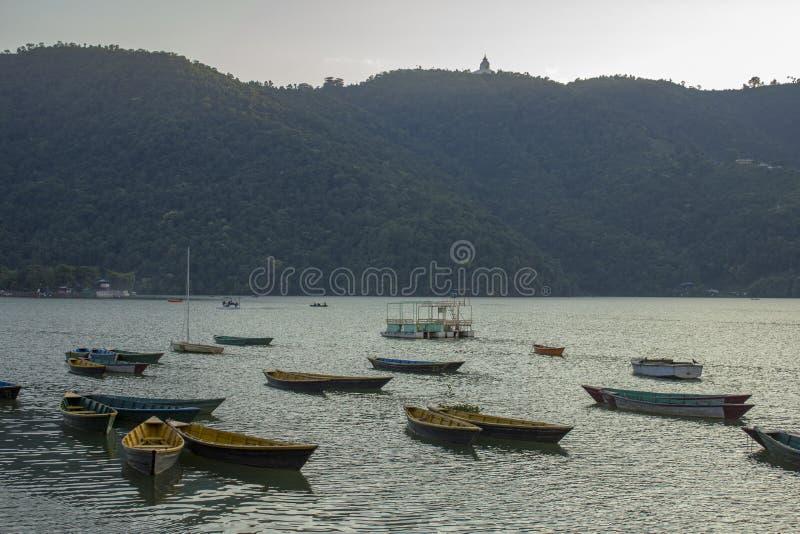 Barcos y catamaranes coloreados brillantes vacíos viejos de madera en el lago Phewa en el fondo de una montaña con un bosque verd foto de archivo
