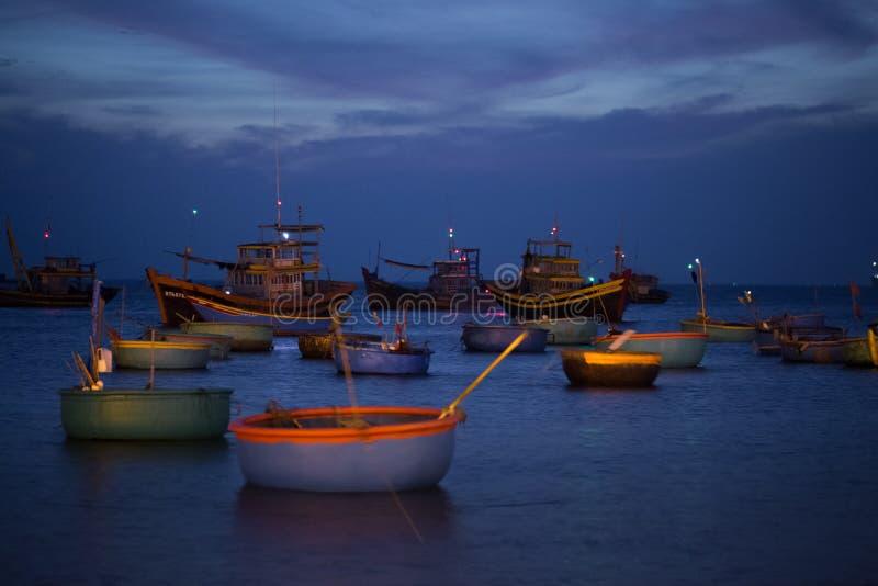 Barcos y cestas de pesca en la puesta del sol imagen de archivo