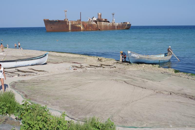 Barcos y redes de los pescadores al lado de un naufragio imagenes de archivo