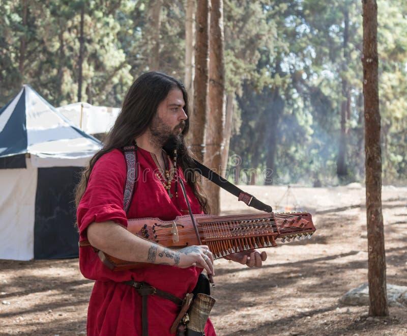 Bard - de deelnemer van de wederopbouw ` Viking Village ` speelt de luit in het kamp in het bos dichtbij Ben Shemen in Israël royalty-vrije stock afbeeldingen