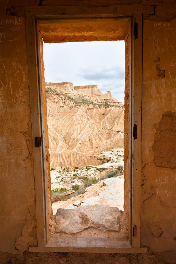 Bardenas Reales view through a door as a frame. The Bárdenas Reales is a semi-desert natural region, or badlands, of some 42,000 hectares (100,000 acres) in stock images