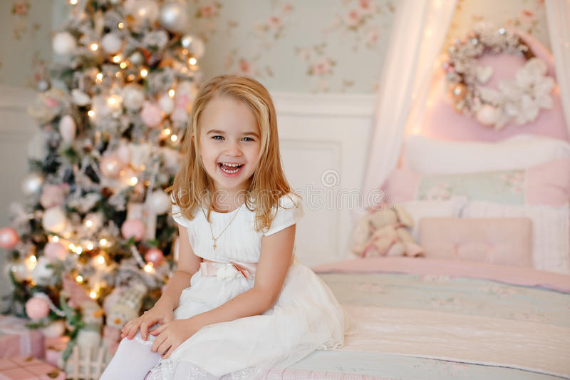 Bardzo ładna powabna małej dziewczynki blondynka w biel sukni obsiadaniu dalej obrazy royalty free