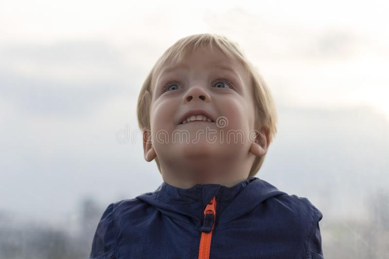 Bardzo śliczna zdziwiona chłopiec Śmieszna chłopiec twarz przyglądająca w górę zamazanego tła przeciw zdjęcie royalty free