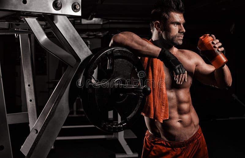 Bardzo mięśniowy sporty facet pije proteinę w ciemnym ciężaru roo zdjęcia stock