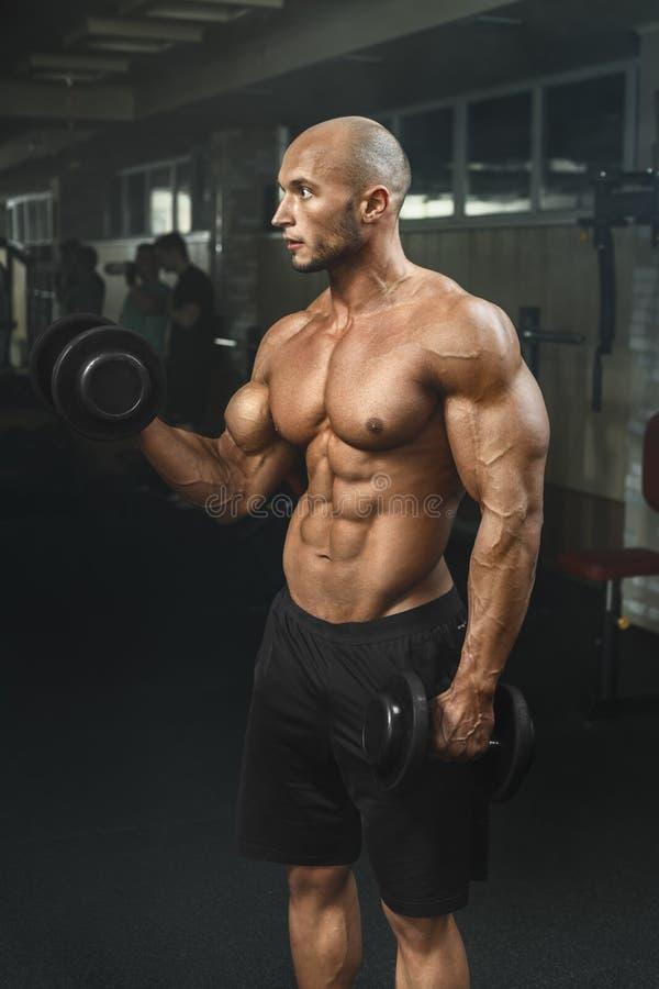 Bardzo potężny sportowy facet pracuje w gym z dumbbells fotografia stock