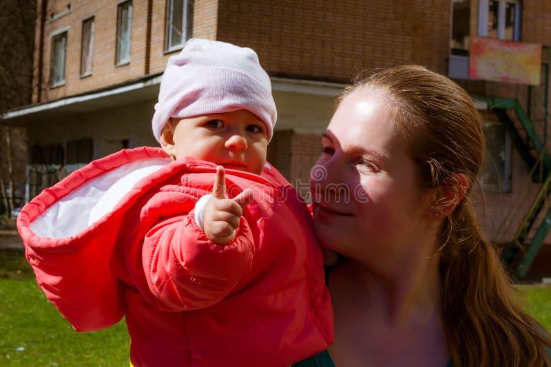 Bardzo poważny dziecko w menchii spojrzeniach w przedstawienia i kamerę palec Siedzi z mamą w ona ręki _ obraz stock