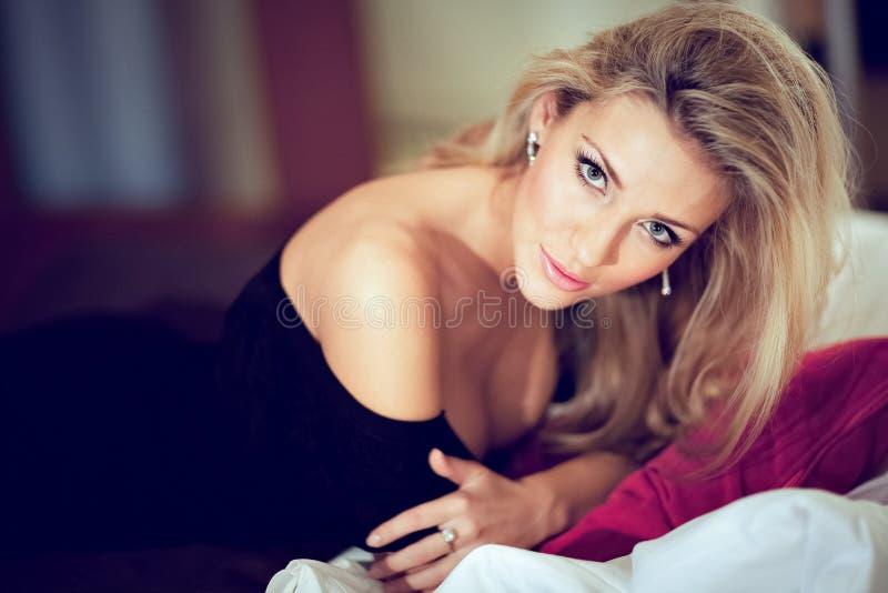 Bardzo seksowna i piękna dziewczyny blondynka w czarnym smokingowym lying on the beach na th obraz royalty free