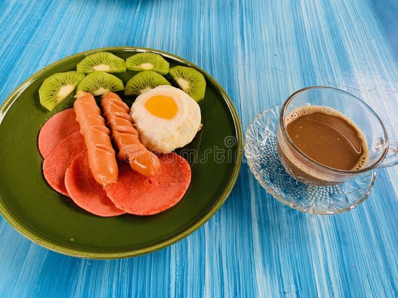 Bardzo smakowity śniadanie Tam jest jajkami, kiełbasami i kiwi, obraz royalty free