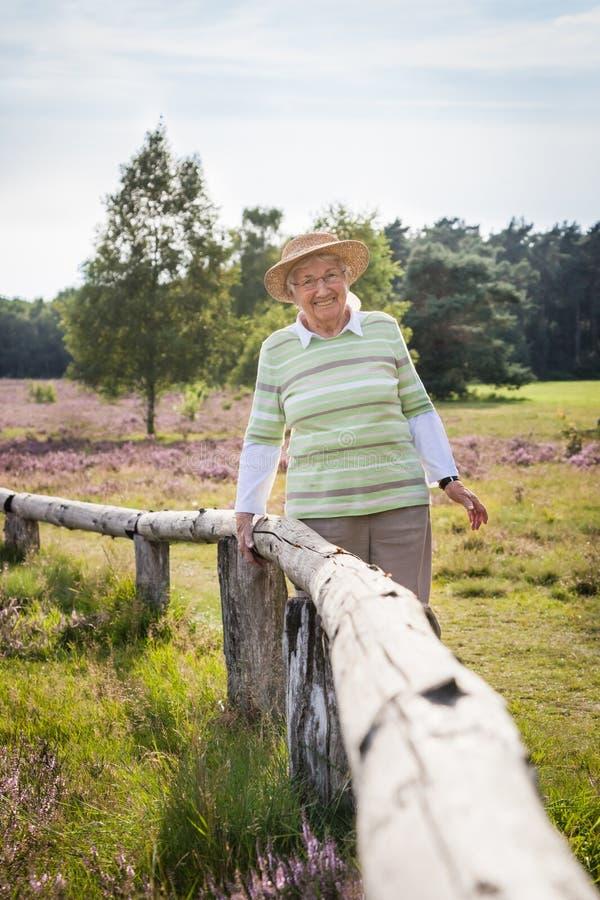 Bardzo stara szczęśliwa starsza kobieta outdoors w wrzosie cumuje, pojęcie dostaje stary szczęśliwy zdrowego zdjęcia stock