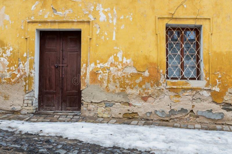 Bardzo stary drzwi i okno w ścianie z obieranie tynkiem zdjęcia royalty free
