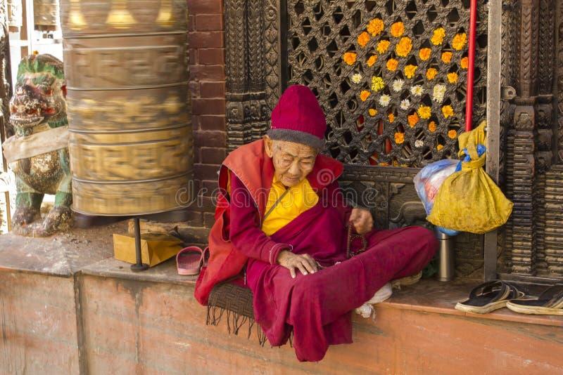 Bardzo stary Tybetański mnich buddyjski w czerwieni i koloru żółtego ubraniach siedzi blisko płodozmiennego modlitewnego bębenu zdjęcie royalty free