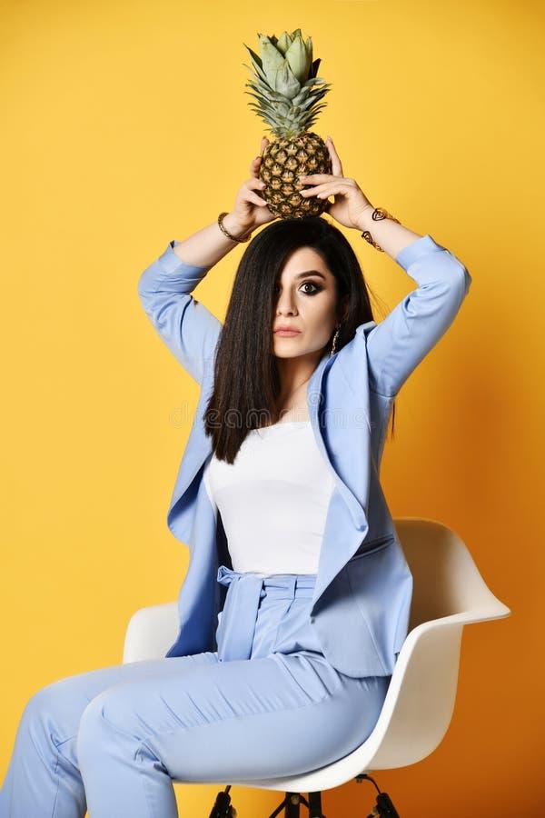 Bardzo zdziwiona biznesowa kobieta w błękitnym oficjalnym kostiumu obsiadaniu w karle trzyma ananasa na jej głowie zdjęcia stock