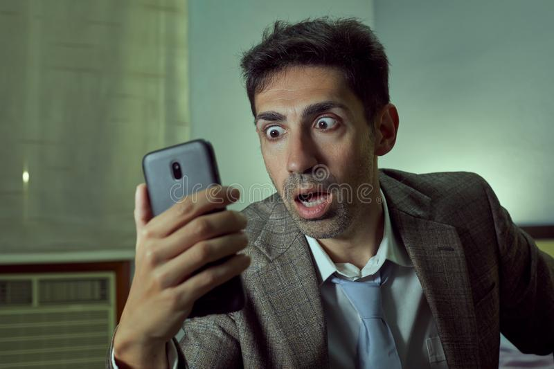 Bardzo zdziwiony mężczyzna patrzeje jego smartphone w pokoju obraz royalty free