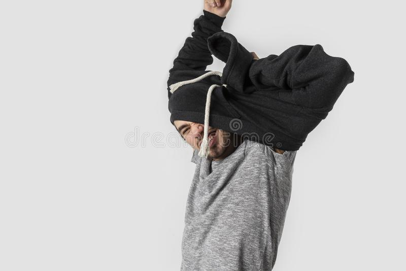 Bardzo zmęczony caucasian młody człowiek szczęśliwie usuwa jego odziewa po tym jak długi i ruchliwie dzień pojedynczy białe tło obrazy stock