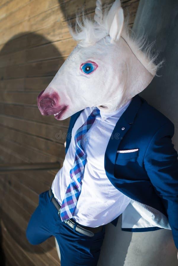 Bardzo zmęczony młody kierownik w eleganckim kostiumu i śmiesznej masce relaksuje na ławce obrazy royalty free
