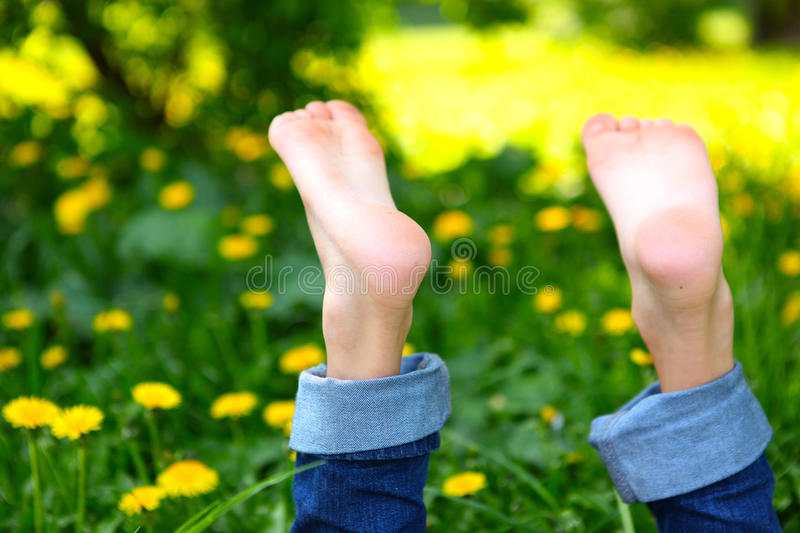Bare boy feet on the summer green grass. With dandelions background stock photo