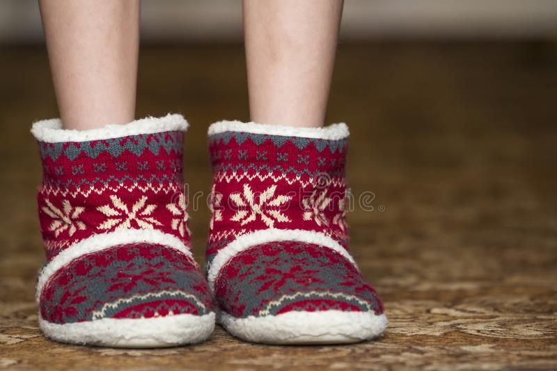 Bare child legs and feet in red winter christmas boots with ornament pattern stock image