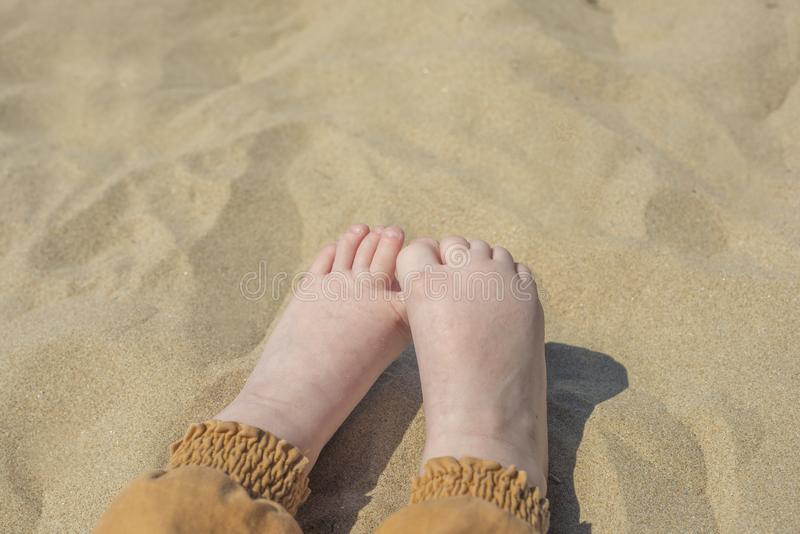 Bare children`s feet on the beach. close-up stock images