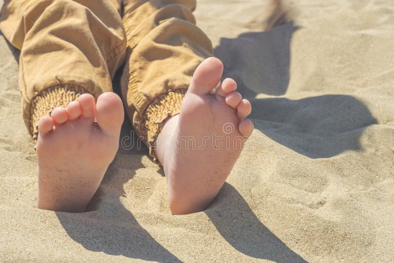 Bare children`s feet on the beach. close-up stock photos
